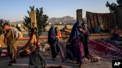 Afghan women walk through a second-hand market where many families sold their belongings before leaving the country or due to financial struggle, in Kabul, Sept. 15, 2021.