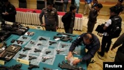 Confiscated weapons are displayed on a table during a news conference at Royal Thai Police headquarters in Bangkok, Oct. 28, 2015. Police widened a major probe into a network of people charged with insulting the monarchy.