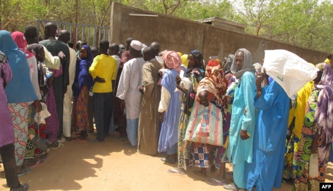 FILE- Cameroonian internally displaced queue at a camp in Kolofata, in the extreme north of Cameroon, for a food distribution provided by the International Red Cross Committee (ICR) on Feb. 22, 2017.
