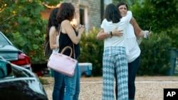 Vecinos consuelas a la madre de uno de los adolescentes desaparecidos cuando salieron a pescar en Tequesta, Florida.
