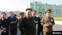 North Korean leader Kim Jong Un gives field guidance at the newly built Wisong Scientists Residential District in this undated photo released by North Korea's Korean Central News Agency (KCNA) in Pyongyang October 14, 2014. Kim, shown using a cane for sup