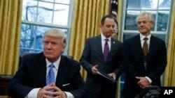 白宫全国贸易委员会主任彼得·纳瓦罗(Peter Navarro,右)等待川普总统签署政令(2017年1月23日)