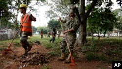 Paraguay Army soldiers clean the backyard of a hospital in an Aedes aegypti mosquito control effort, in Asuncion, Paraguay, Tuesday, Feb. 2, 2016. (AP Photo/Jorge Saenz)
