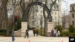 In this Friday, April 29, 2016, photo, people stand near the entrance gate to Northwestern University in Evanston, Ill. (Chris Walker/Chicago Tribune via AP)