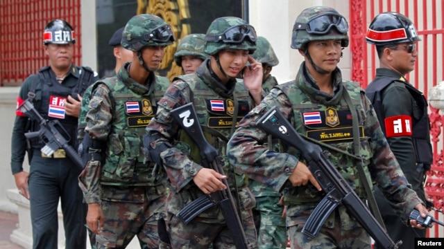 FILE - Soldiers patrol around the Royal Thai Army Headquarters as members of the Radio and Satellite Broadcasters gather in Bangkok, June 18, 2014.
