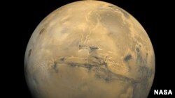 File - The largest canyon in the Solar System cuts a wide swath across the face of Mars. Named Valles Marineris, the grand valley extends more than 3,000 kilometers long, spans as much as 600 kilometers across, and delves as much as 8 kilometers deep. Photo Cred