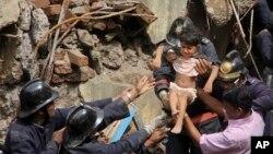 27일 인도 뭄바이에서 발생한 고층 아파트 붕괴 현장에서 소방관들이 어린이를 구조하고 있다.