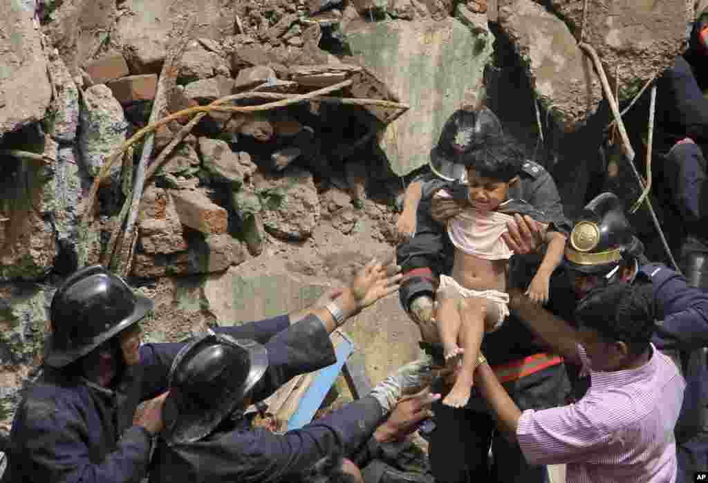 Para petugas pemadam kebakaran menyelamatkan seorang anak perempuan dari reruntuhan gedung yang ambruk di Mumbai (27/9). Pihak berwenang telah menghentikan pencarian Minggu (29/9) dan data korban tewas resmi adalah 60 orang.