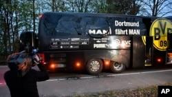 Un cameraman filamant le bus du Borussia Dortmund après l'explosion qui à endommagé le bus avant le match des quarts de finale de la ligue des champions contre l'AS Monaco, Allemagne le 11 avril 2017 (AP Photo/Martin Meissner)