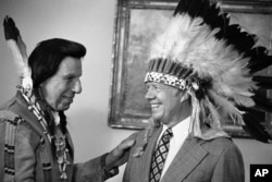 FILE - This photo shows Iron Eyes Cody, who fabricated Native American identity, presenting former President Jimmy Carter with a Native American headdress in the Oval Office in Washington on April 21, 1978. Cody, an Italian American, also gave Carter a Na