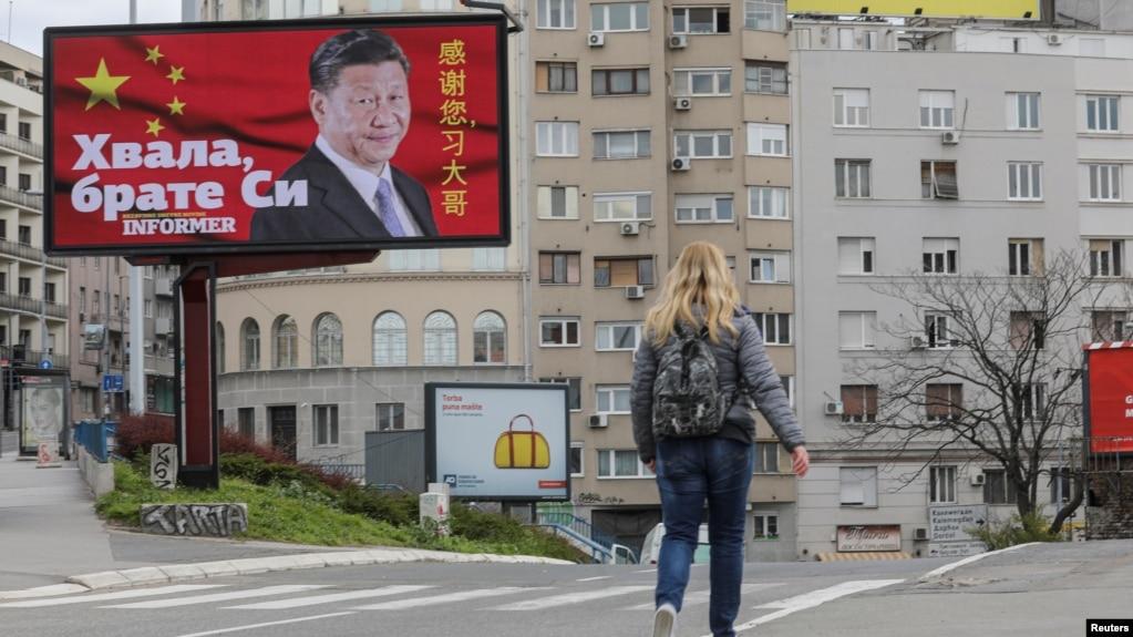 塞尔维亚一名女子走过贝尔格莱德街头树立的感谢中国领导人习近平的广告牌旁。(2020年4月1日)