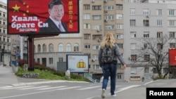 塞爾維亞一名女子走過貝爾格萊德街頭樹立的感謝中國領導人習近平的廣告牌旁。(2020年4月1日)
