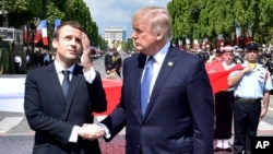 French President Emmanuel Macron, left, shakes hands with President Donald Trump after the Bastille Day military parade in Paris, July 14, 2017.