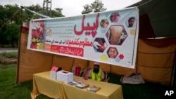 ایک شخص حافظ سعید کی فلاح انسانیت فاونڈیشن کے چندہ جمع کرنے کے اسٹال پر بیٹھا ہے (فائل)