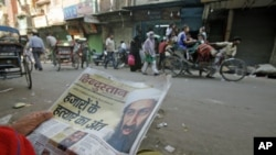 A man reads a local newspaper reporting the death of al-Qaida leader Osama bin Laden in the old quarters of Delhi, May 3, 2011
