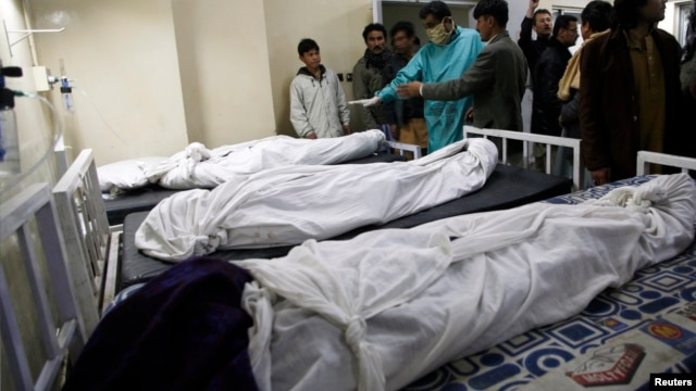 Paramedics and families stand near victims of a bomb attack in a Shi'ite Muslim area, at a hospital in Quetta, Feb. 16, 2013.
