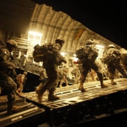 United States soldiers board a plane at Baghdad International Airport in July to start their trip home
