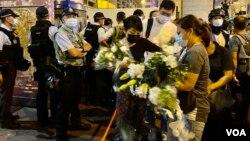立法会议员毛孟静(戴黑口罩者)8月31日晚在太子地铁站出口外协助市民献花纪念8-31事件一周年。 (美国之音/汤惠芸)