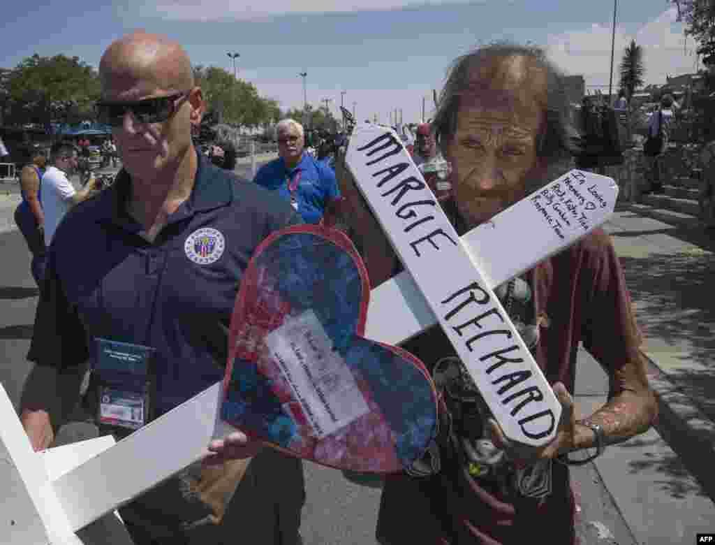 Antonio Basbo (R) holds the cross of his common-law wife Margie Reckard who died in the shooting as he walks to a makeshift memorial in El Paso, Texas, Aug. 5, 2019, two days after the shooting that left 22 people dead at the Cielo Vista Mall WalMart.