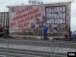 一名男子在莫斯科支持政治犯集会上演讲。他身后的背景是被关押和流亡的政治犯照片,幕墙上的字是释放去年5月6日示威的被捕人士。(美国之音白桦拍摄)