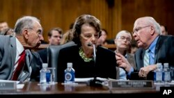 Senate Judiciary Committee Chairman Chuck Grassley, R-Iowa, left, accompanied by Sen. Dianne Feinstein, D-Calif., the ranking member, center, speaks with Sen. Patrick Leahy, D-Vt., right, during a Senate Judiciary Committee markup meeting on Capitol Hill,