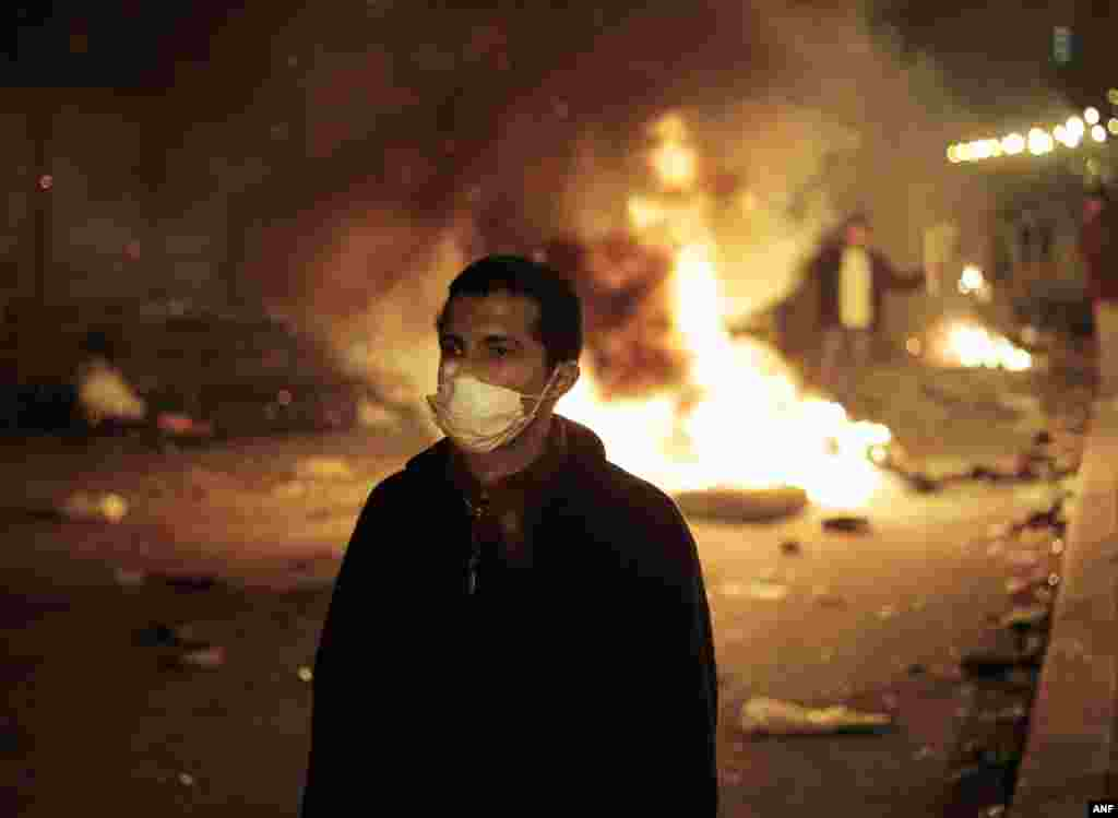 An anti-government protester is backdropped by a fire set up by protesters near the Tahrir Square Jan. 28, 2011.
