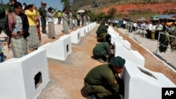In this photo released by the Myanmar Defense Ministry, soldiers place urns containing ashes of soldiers fallen during recent fighting against ethnic Kokang rebels at a military funeral in Lashio, Myanmar, Feb. 23, 2015.