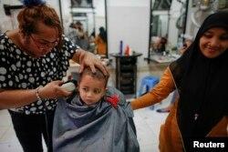 Francisca (kiri), seorang anggota komunitas transpuan, sedang memotong rambut anak kecil di salon tempat dia bekerja di Banda Aceh, 10 Desember 2012. (Foto: Reuters)