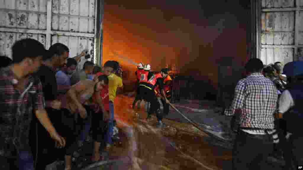 Firefighters try to extinguish fire after a cleaning materials factory was hit by an Israeli airstrike in Gaza City, Aug. 10, 2014.