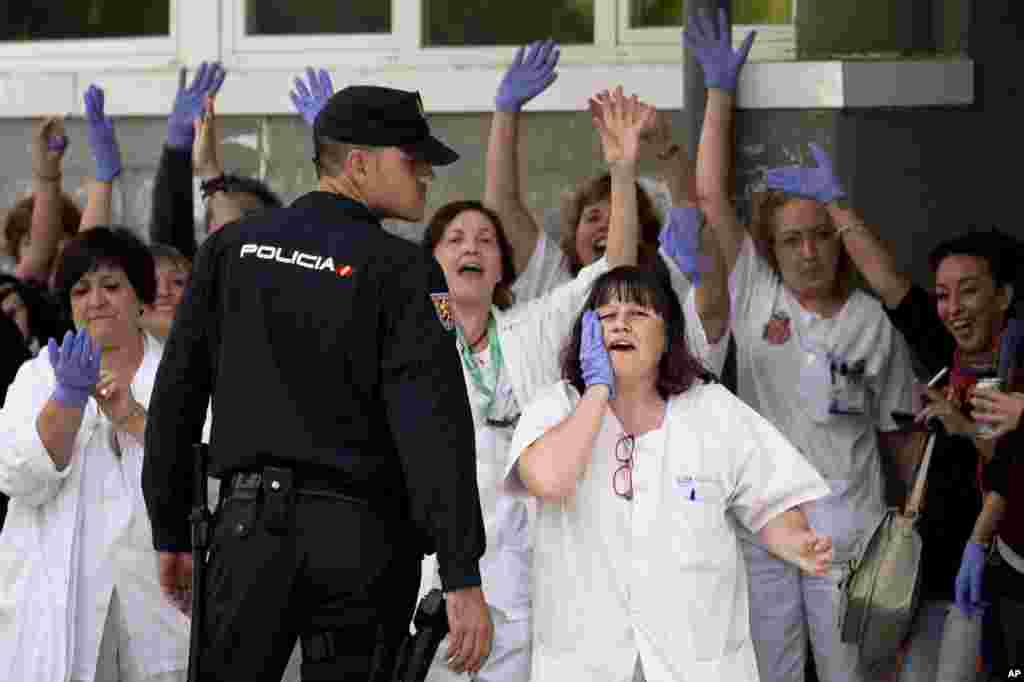 Medical practitioners call out to Spanish Prime Minister Mariano Rajoy during his visit to the Carlos III hospital in Madrid, Spain, Oct. 10, 2014.