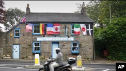 Një motoçiklist kalon përpara klubit të stolisur me flamujt e vendeve të G-7ës (Cornwall, Angli, 9 qershor 2021)