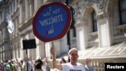 Seorang demonstran anti-lockdown dan anti-vaksin memegang plakat dalam aksi protes di Downing Street, di tengah pandemi COVID-19, London, Inggris, 14 Juni 2021. (REUTERS/Henry Nicholls)