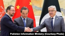 Pakistani Foreign Minister Khawaja Asif shakes hand with Afghan Foreign Minister Salahuddin Rabbani in Beijing, Dec. 26, 2017.