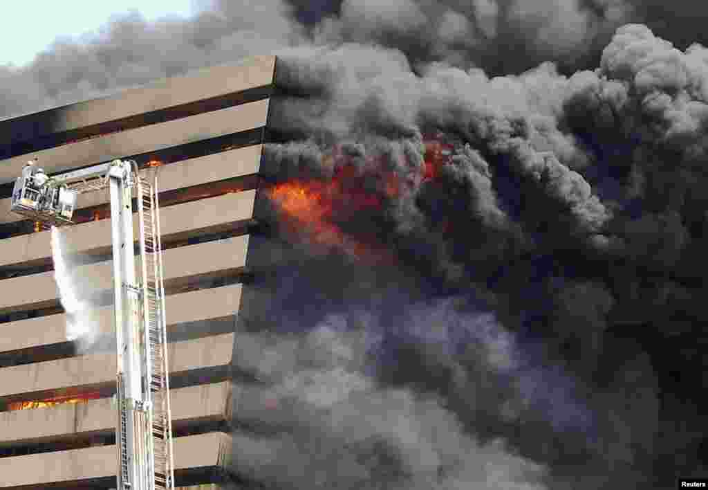 Firefighters try to douse the flames after a fire broke out in a commercial building at a textile market in Surat in the western Indian state of Gujarat. The cause of the fire is being investigated and no causality have been reported, fire officials said.