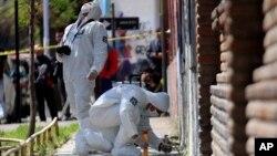 Peritos buscan evidencia en el lugar donde explotó una bomba en Santiago la madrugada del jueves.