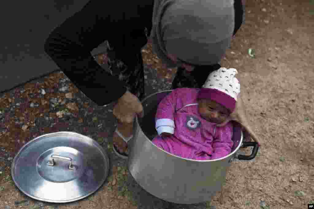 Seorang perempuan Suriah membawa bayinya dengan panci untuk memasak di kamp Ritsona utara Athena, Yunani.