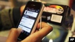Anh Robert Drayton dùng chiếc điện thoại thông minh của mình để tìm mua quà và so sánh giá cả, 28/11/2012. (AP Photo/Seth Wenig)