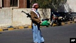 一名胡塞反叛武裝守衛著總統府外