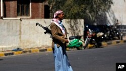 An armed Houthi Shi'ite Yemeni stands guard outside the Republican Palace in Sana'a, Feb. 16, 2015.