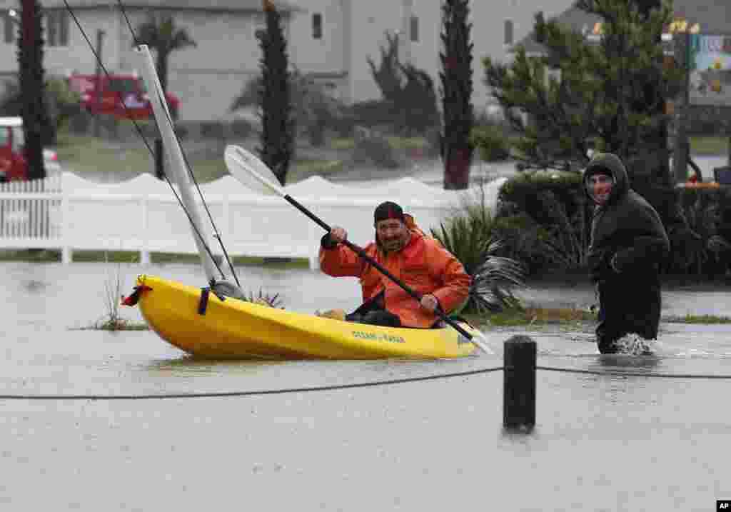 Un hombre rema en las aguas provocadas por las inundaciones en Kitty Hawk, Carolina del Norte.