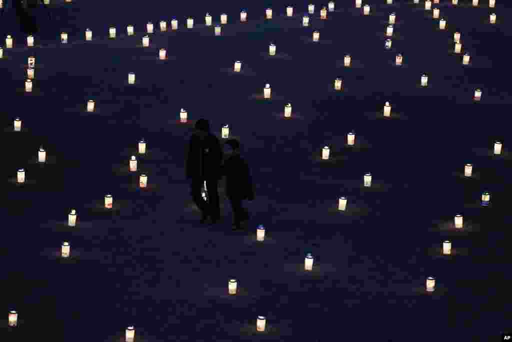 Boys walks past lanterns at a candlelight memorial held in remembrance of victims of the March 11, 2011 earthquake and tsunami in Iwaki, Fukushima prefecture, March 11, 2012. (Reuters)