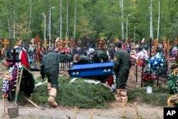 Grave diggers wearing protective suits carry a coffin of a COVID-19 victim for burial in the section of a cemetery reserved for coronavirus victims, outside Moscow, Russia, Tuesday, May 26, 2020.