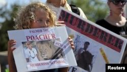Seorang warga di Bloomington, Minnesota, memegang tanda dalam sebuah aksi protes di luar klinik gigi milik Walter Palmer (29/7).