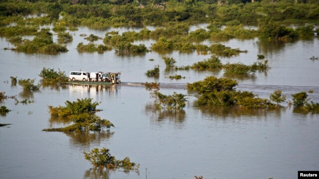 A barge transports vehicles across the River Niger channel in Lokoja, Kogi State, following flooding along the River Niger and Benue confluence in central Nigeria, Sept. 24, 2012.