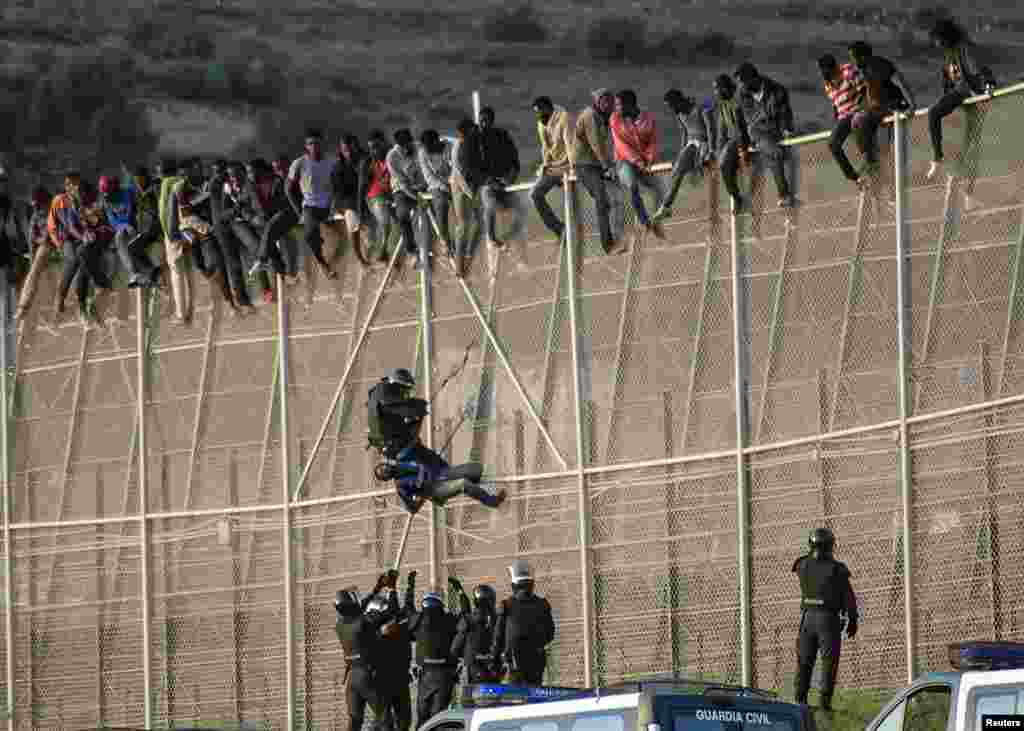 A Spanish Civil Guard pulls an African migrant from a border fence during an attempt to cross into Spanish territories, between Morocco and Spain's north African enclave of Melilla.
