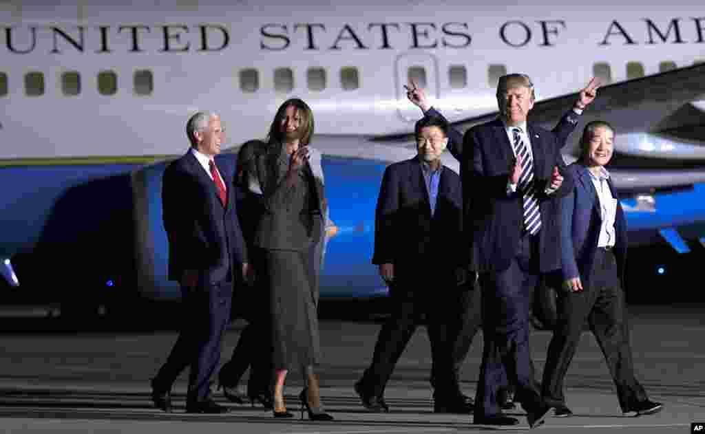 Президент США Дональд Трамп идет вместе с Тони Кимом (третий справа), Ким Дон Чхолем (справа) иКим Хак Соном (позади Трампа)–тремя освобожденными из северокорейских тюрем американскими гражданами