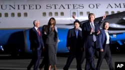 President Donald Trump walks with Tony Kim, third right, Kim Dong Chul, right, and Kim Hak Song, behind Trump, the three Americans detained in North Korea, as they arrive at Andrews Air Force Base in Md., May 10, 2018. Walking with Trump is Vice President