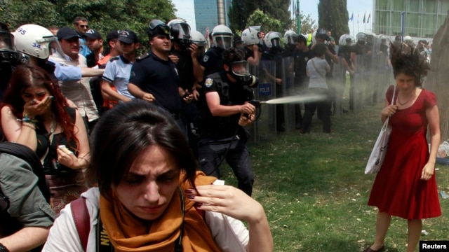 A Turkish riot policeman uses tear gas as people protest against the destruction of trees in a park brought about by a pedestrian project, in Taksim Square in central Istanbul, May 28, 2013.