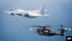 美军一架MH-53E海龙式直升机与一架KC-130加油机在维吉尼亚州诺福克海军基地附近上空进行演练。(2016年3月资料照)