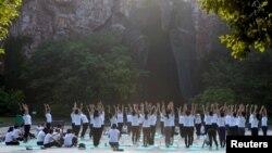 中国江苏淮安市钵池山公园的巨型老子雕像前,人们在国际瑜伽日练习瑜伽(2018年6月21日)